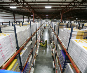 Warehouse racking with product and a forklift driver